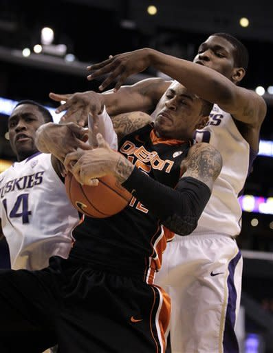 Oregon State's Eric Moreland, center, and Washington's Tony Wroten, left, and Shawn Kemp, Jr. fight for a rebound during the first half of an NCAA college basketball game at the Pac-12 conference championship in Los Angeles, Thursday, March 8, 2012. (AP Photo/Jae C. Hong)