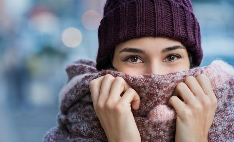 Winter portrait of young beautiful woman covering face with woolen scarf. Closeup of happy girl feeling cold outdoor in the city. Young woman holding scarf and looking at camera. (Winter portrait of young beautiful woman covering face with woolen sca