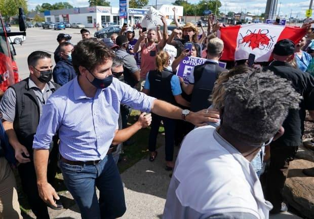 Liberal Leader Justin Trudeau, left, is escorted by his RCMP security detail past protesters as he arrives for a campaign stop in Brantford, Ont. on Monday, Sept. 6, 2021. (Nathan Denette/The Canadian Press - image credit)