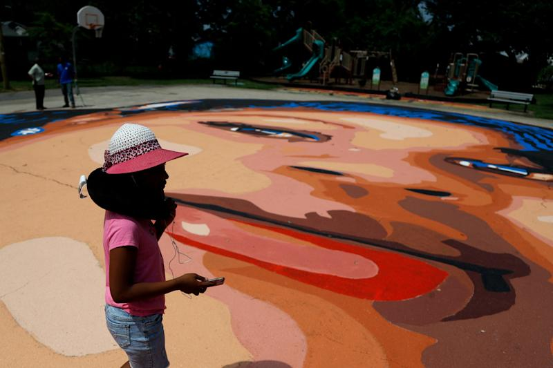 Saniyah Womack, 9, walks on a ground mural depicting a portrait of Breonna Taylor at Chambers Park, Monday, July 6, 2020, in Annapolis, Md. The mural honors Taylor, a 26-year old Black woman who was fatally shot by police in her Louisville, Kentucky, apartment. The artwork was a team effort by the Banneker-Douglass Museum, the Maryland Commission on African American History and Culture, and Future History Now, a youth organization that focuses on mural projects. (AP Photo/Julio Cortez)