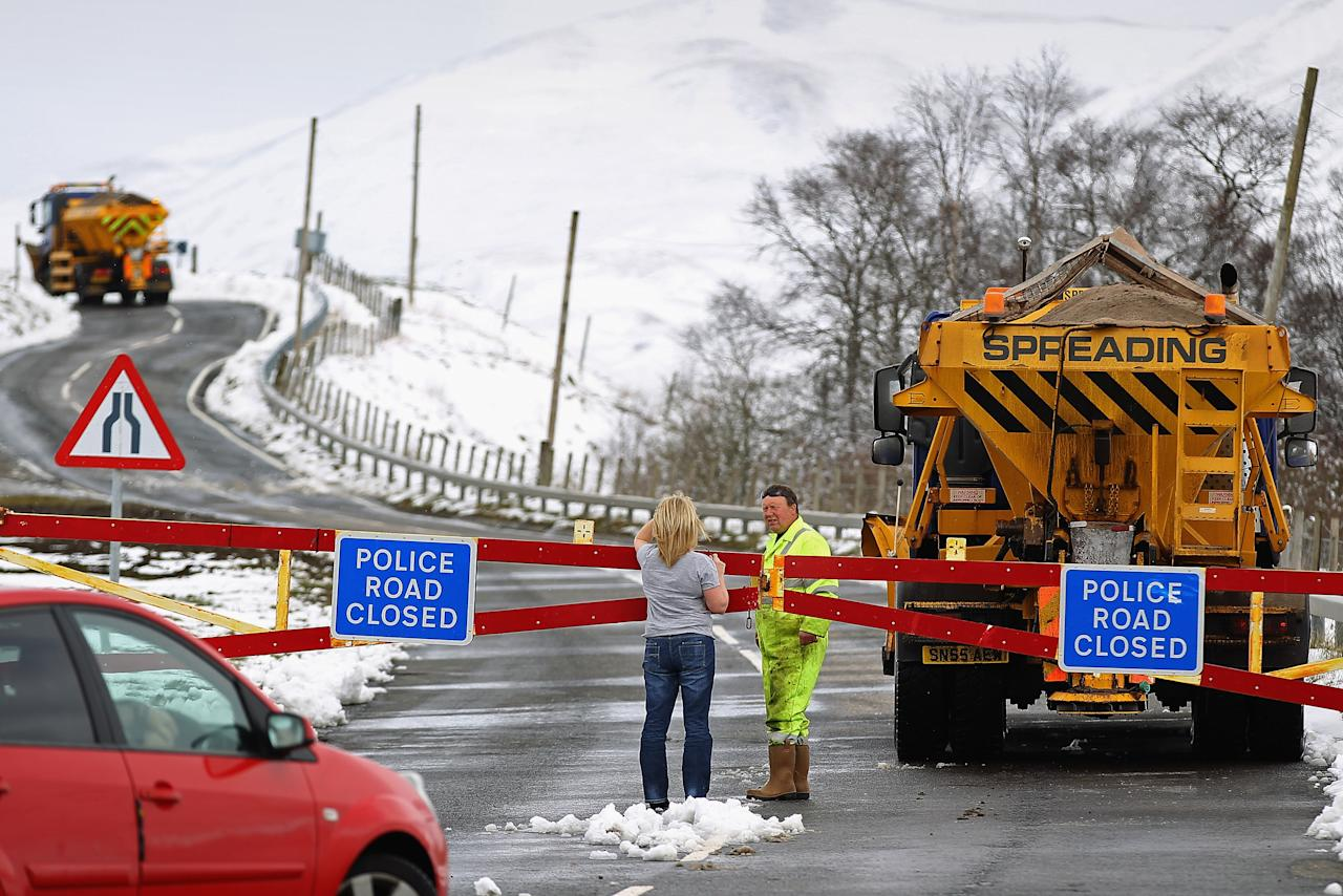 SPITTAL OF GLENSHEE, SCOTLAND - APRIL 03:  A woman talks with a gritter driver working on a closed road on April 3, 2012 in Spittal of Glenshee, Scotland. Snow has returned to parts of Scotland just a week after the country experienced record high temperatures for March. (Photo by Jeff J Mitchell/Getty Images)