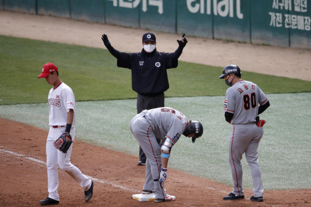 FILE - In this Tuesday, May 5, 2020, file photo, first base umpire Lee Ki-joong, wearing a mask and gloves as a precaution against the new coronavirus, makes a call during a baseball game between Hanwha Eagles and SK Wyverns in Incheon, South Korea. Zimmerman is offering his thoughts as told to AP in a diary of sorts while waiting for the 2020 season to begin. In the sixth installment, he discusses the return to American TV of baseball -- South Korean baseball. (AP Photo/Lee Jin-man, File)