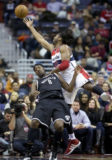 Washington Wizards Nene (42) of Brazil lays up and is fouled by Brooklyn Nets' Andray Blatche (0) during the first half of an NBA basketball game in Washington, Friday, Jan. 4, 2013. (AP Photo/Manuel Balce Ceneta)