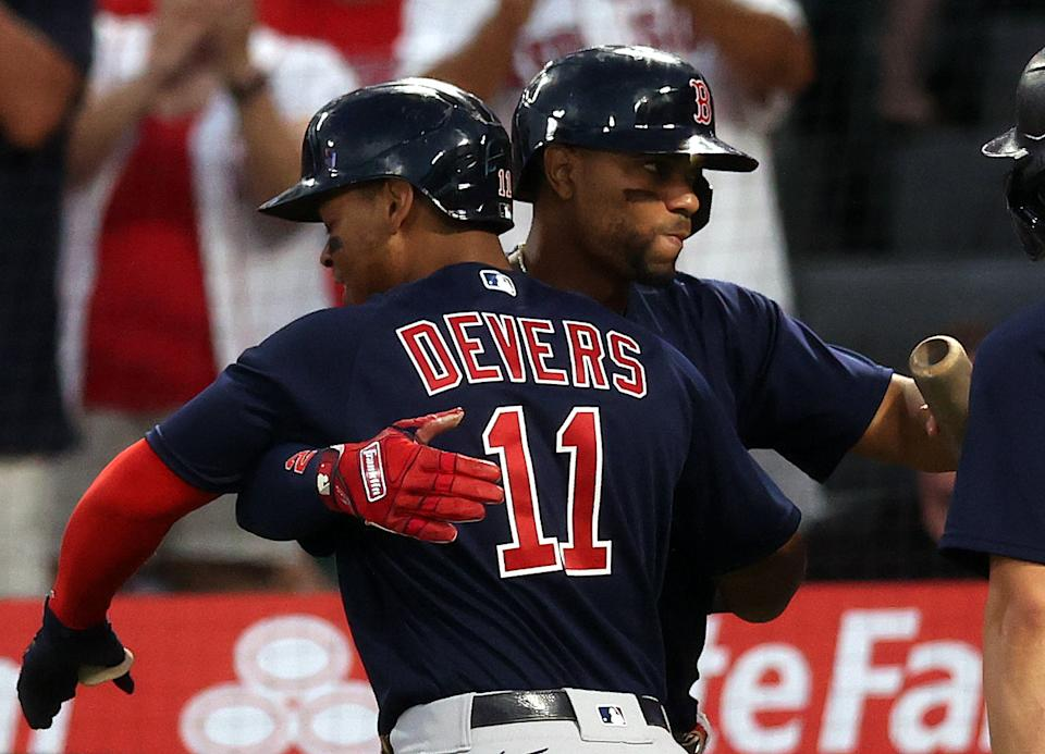 Rafael Devers #11 of the Boston Red Sox celebrates a two-run home run with Xander Bogaerts #2