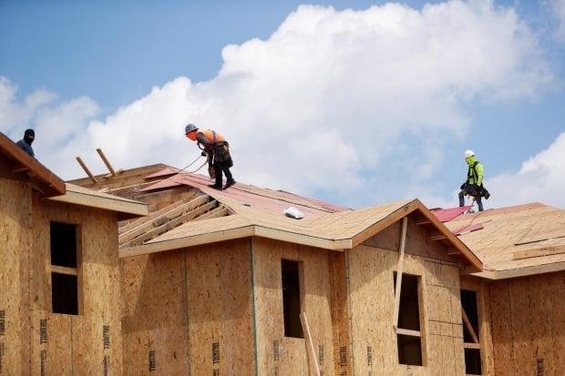 Carpenters work on constructing new townhomes while building material supplies are in high demand, in Tampa, Fla., on May 5. In a rush to fill the demand, builders help to drive up the price of lumber and skilled wages, which might be part of a wider trend. (Octavio Jones/Reuters - image credit)