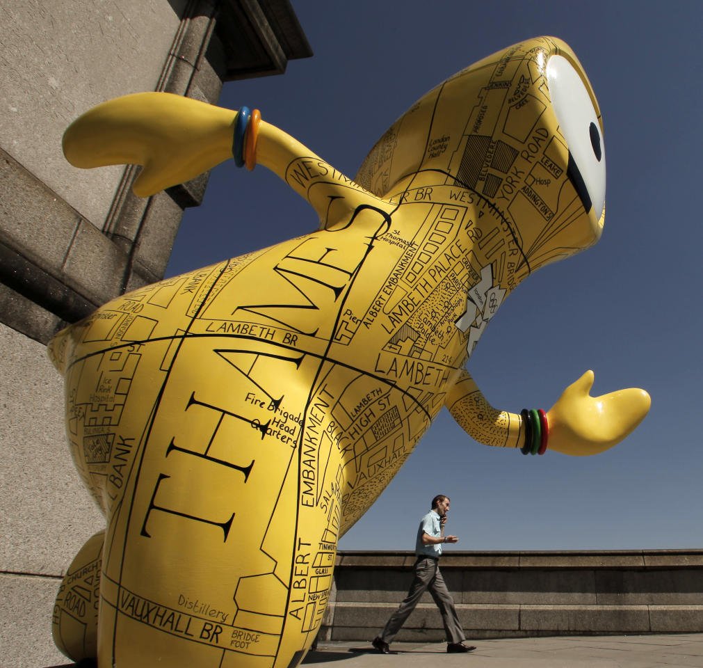 A man walks past an Olympic mascot statue painted in the likeness of a map Monday, July 23, 2012, in London. The statue is one of 84 fiberglass sculptures of the mascots Wenlock or Mandeville that were painted by various artists and erected across the city for the 2012 London Olympic Games. (AP Photo/Charlie Riedel)