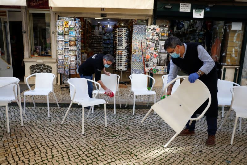 Workers clean chairs to open a restaurant terrace on the first day of the reopening after a country lockdown, amid the coronavirus disease (COVID-19) pandemic, in Lisbon
