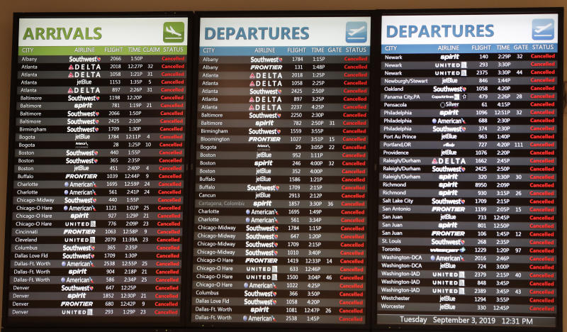 Flight information monitors show all flights cancelled as Orlando International Airport closed due to the anticipated arrival of Hurricane Dorian on the East Coast Tuesday, Sept. 3, 2019, in Orlando, Fla. (AP Photo/John Raoux)