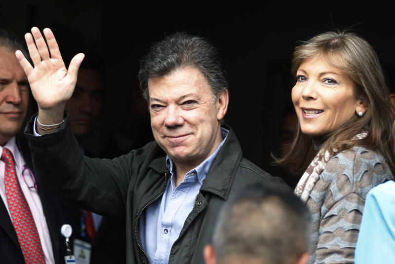 Colombia's President Juan Manuel Santos waves upon his arrival to the Santa Fe's Clinic Foundation to undergo surgery to remove a prostate tumor accompanied by his wife Maria Clemencia Rodriguez, right, in Bogota, Colombia, Wednesday, Oct. 3, 2012. (AP Photo/Fernando Vergara)