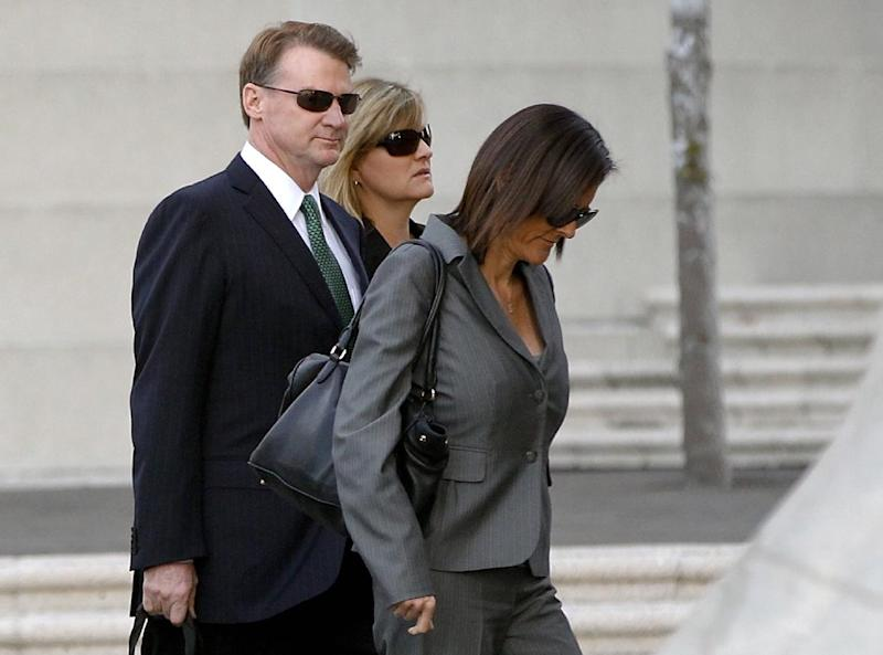 Former Deutsche Bank executive Brian Mulligan, left, arrives with his wife Victoria, center, at the Edward R. Roybal Federal Building, Tuesday, Jan. 21, 2014, in Los Angeles. A trial began for Mulligan, who sued the city of Los Angeles and two police officers claiming they beat him during a bizarre incident in May 2012. He is seeking $20 million in damages in a lawsuit filed in federal court. Officers said Mulligan told them he had ingested a type of bath salts known as White Lightning. Mulligan, who has no prior criminal record, once served as co-chairman of Universal Studios and chief financial officer of Seagram Co. (AP Photo/Damian Dovarganes)