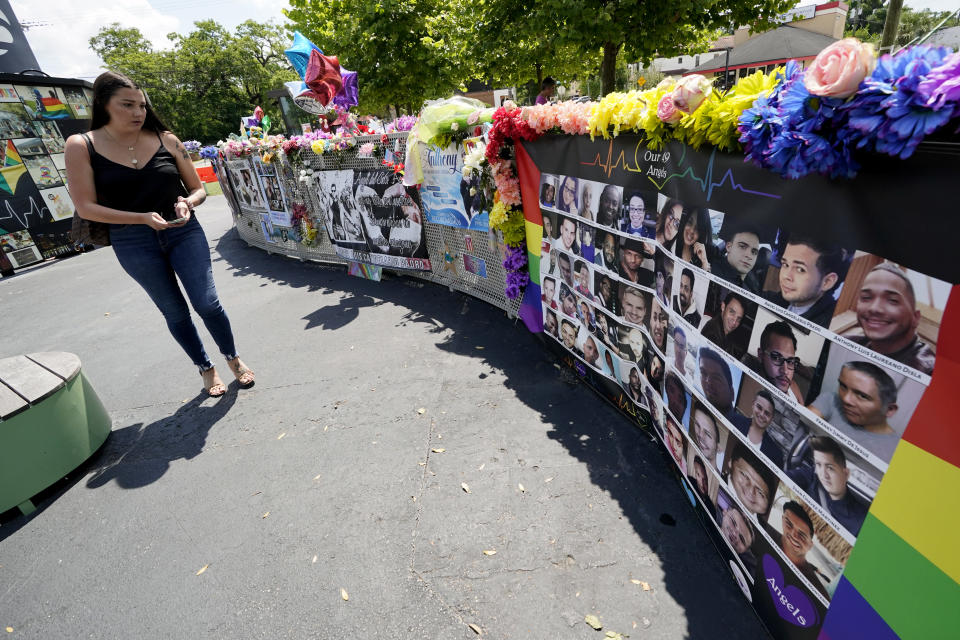 A visitor looks over a display with the photos and names of the 49 victims that died at the Pulse nightclub memorial Friday, June 11, 2021, in Orlando, Fla. Saturday will mark the fifth anniversary of the mass shooting at the site. (AP Photo/John Raoux)