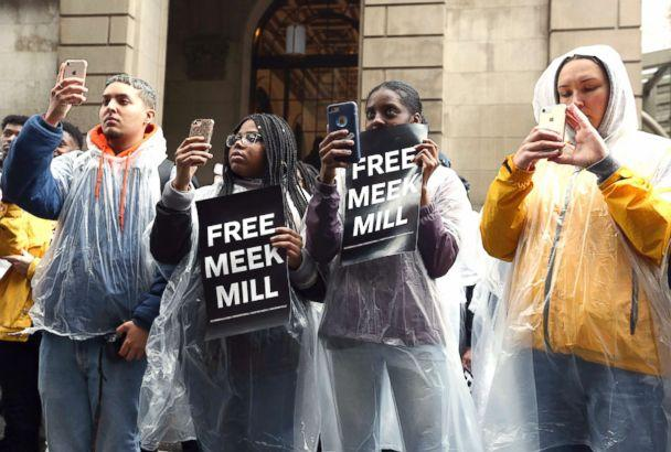 PHOTO: Protesters uses their phones and listen to a speaker in front of a courthouse during a hearing for rapper Meek Mill, April 16, 2018 in Philadelphia. (Jacqueline Larma/AP)