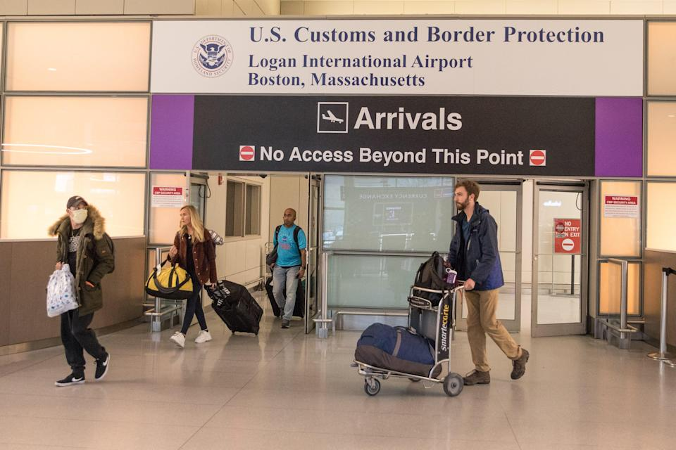 Passengers leave the secure area in the arrivals area of the international terminal at Logan Airport on March 13, 2020 in Boston, Massachusetts.