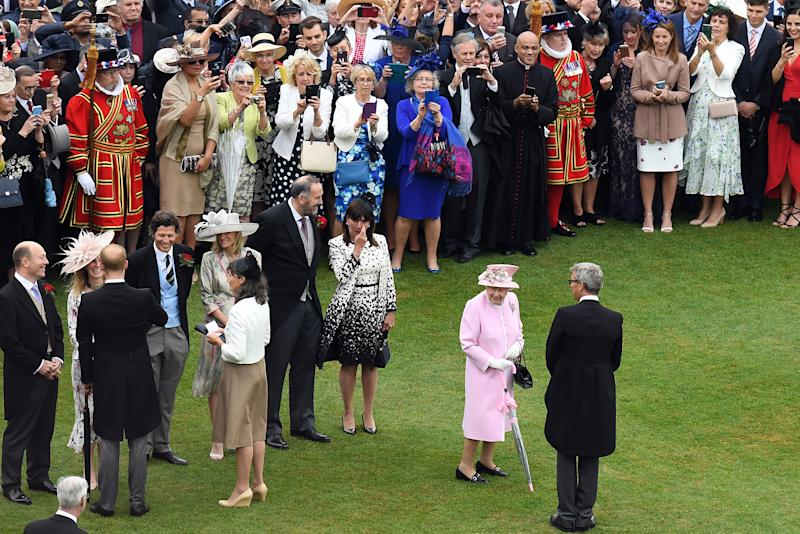 Britain's Queen Elizabeth II and Britain's Prince Harry, Duke of Sussex greet guests at the Queen's Garden Party in Buckingham Palace, central London on May 29, 2019. (Photo by Stuart C. Wilson / POOL / AFP) (Photo credit should read STUART C. WILSON/AFP via Getty Images)