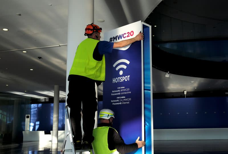 Employees place a banner with information of MWC20 in Barcelona