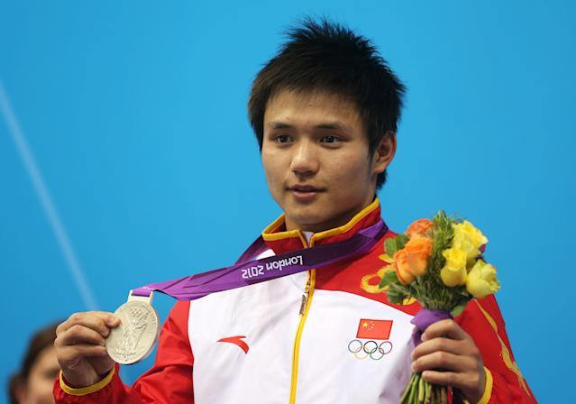 LONDON, ENGLAND - AUGUST 11: Silver medallist Bo Qui of China celebrates on the podium during the medal ceremony for the Men's 10m Platform Diving Semifinal on Day 15 of the London 2012 Olympic Games at the Aquatics Centre on August 11, 2012 in London, England. (Photo by Clive Rose/Getty Images)