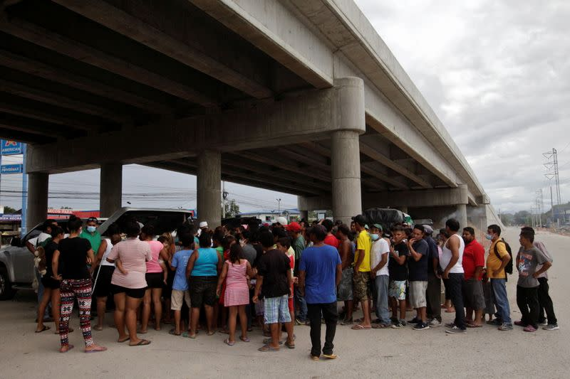 People queue for food under an overpass, where they are sheltered along other residents that lost their homes due to the floods caused by heavy rain brought by Storm Iota, in San Pedro Sula