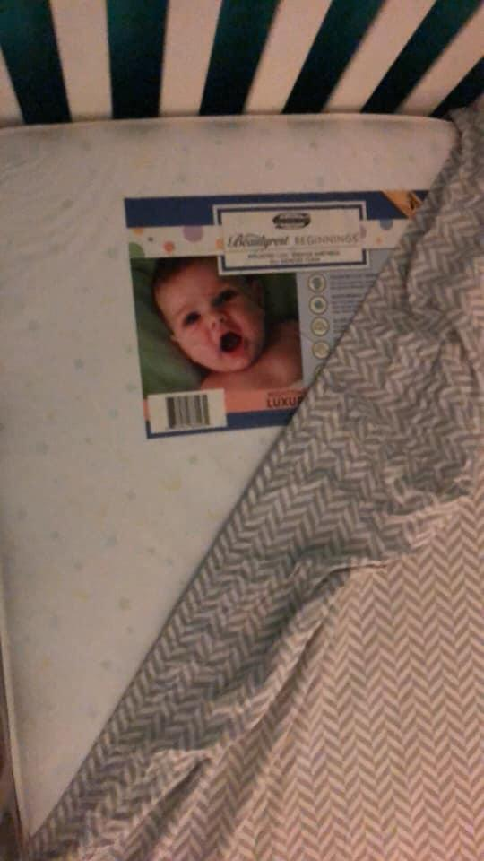 Daylight reveals under the sheet the image of the crying baby to be a label on the mattress.