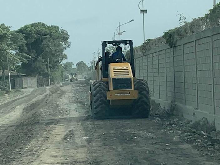 Workers prepare an unpaved road on Wednesday, July 21, 2021, for guests who will be attending the funeral of the late Haiti President Jovenel Moïse at his family's walled-in residence on the outskirts of the northern port city of Cap-Haïtien, Haiti, on Friday, July 23.