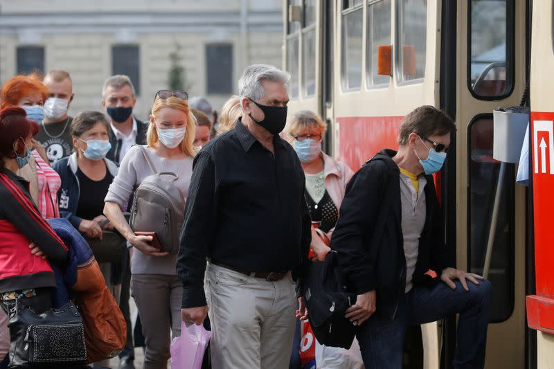 People wearing protective face masks get on a tram in Kyiv