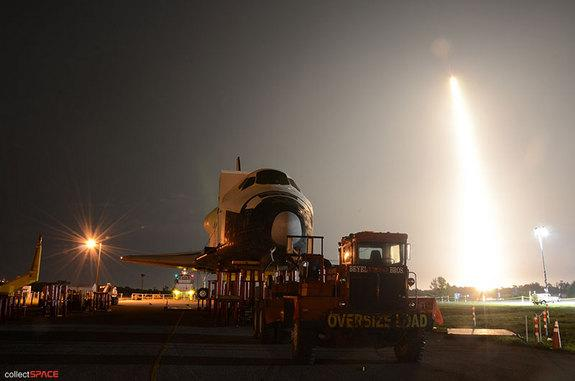SpaceX's first space station-bound Dragon spacecraft, flying atop a Falcon 9 rocket, launches behind a high fidelity mockup of the space shuttle, NASA's previous means of delivering cargo to International Space Station. Liftoff occurred on May