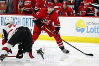 Carolina Hurricanes' Warren Foegele (13) looks to pass the puck over Ottawa Senators' Thomas Chabot (72) during the second period of an NHL hockey game in Raleigh, N.C., Monday, Nov. 11, 2019. (AP Photo/Karl B DeBlaker)