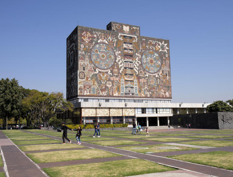 Mexico City, Mexico, January 8, 2020. Mexico city University campus library iconic facade created by the Mexican artist Juan O'Gorman with people walking by