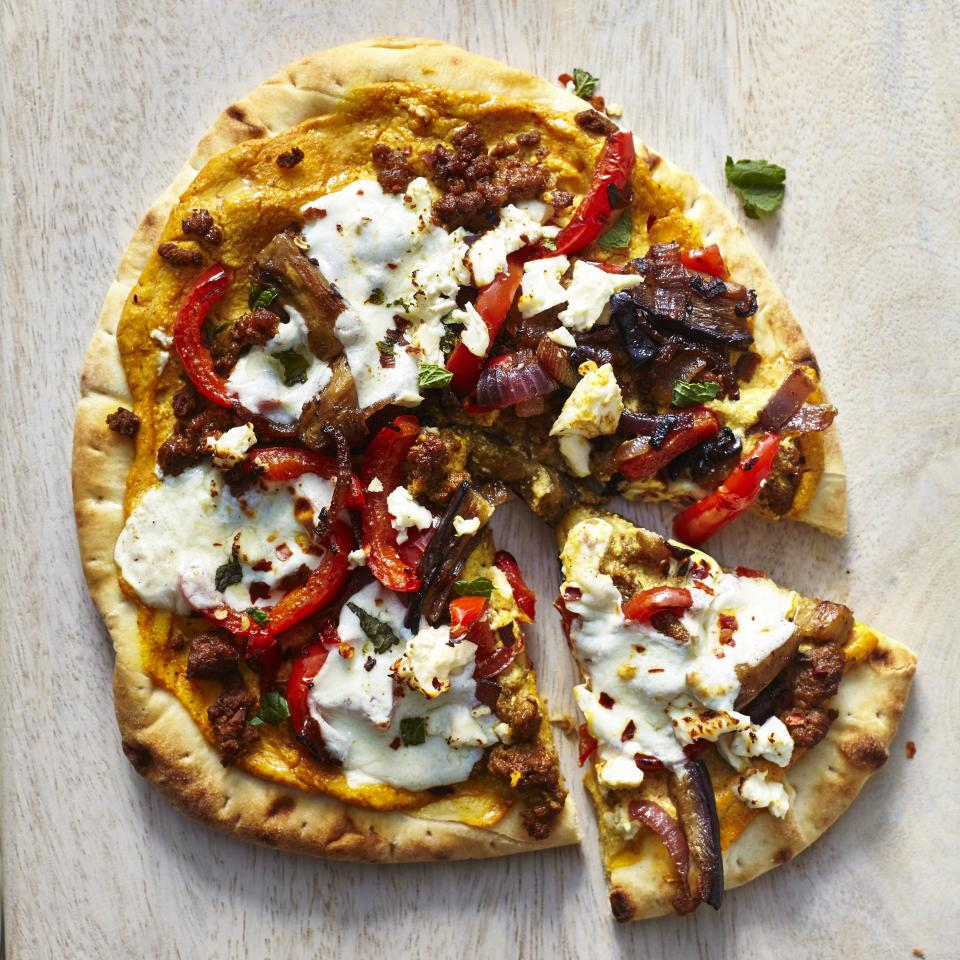 """<p>This pizza is loaded with fantastic tandoori flavor and ground lamb, giving it an authentic edge and creating one big burst of flavors all on one pizza. The <a href=""""https://www.myrecipes.com/recipe/tandoori-spice-blend"""">Tandoori Spice Blend</a> used here consists of items that you probably already have in your spice cabinet such as paprika, cayenne pepper, and coriander, which give this pizza a really great flavor. Also, instead of kneading your own pizza dough, uses store-bought naan bread as a convenient time-saver. </p> <p><a href=""""https://www.myrecipes.com/recipe/tandoori-lamb-pizza"""">Tandoori Lamb Pizza Recipe</a></p>"""
