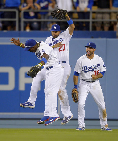 Los Angeles Dodgers center fielder Matt Kemp, center, celebrates with right fielder Yasiel Puig, left, as right fielder Andre Ethier looks on after making a catch on a ball hit by San Francisco Giants' Marco Scutaro to end their baseball game, Tuesday, June 25, 2013, in Los Angeles. The Dodgers beat the Giants 6-5. (AP Photo/Mark J. Terrill)