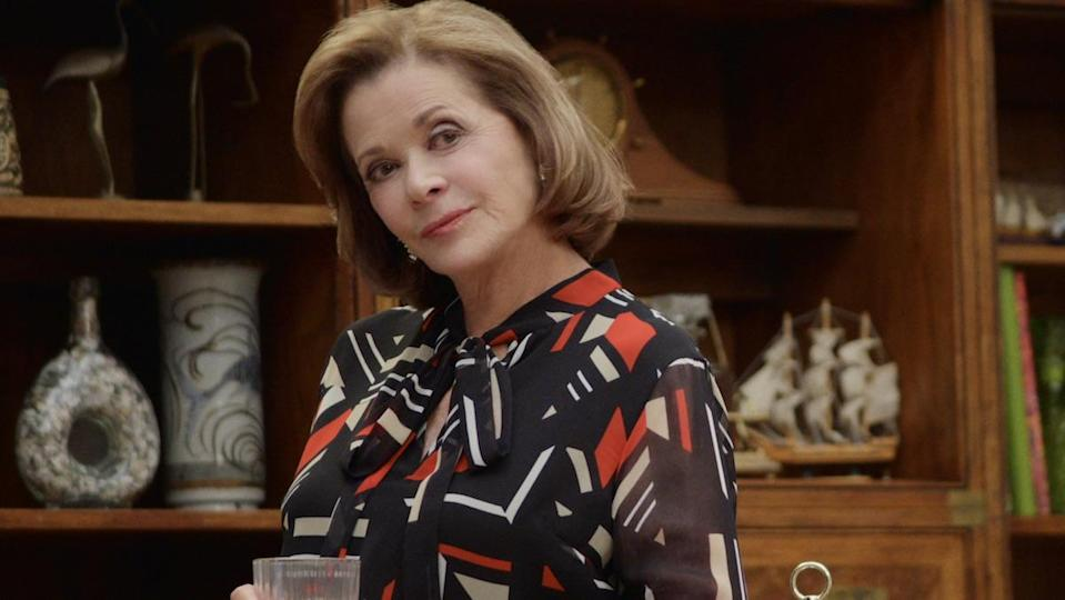 Jessica Walter as Lucille Bluth holding a glass in front of a bookcase on Arrested Development.