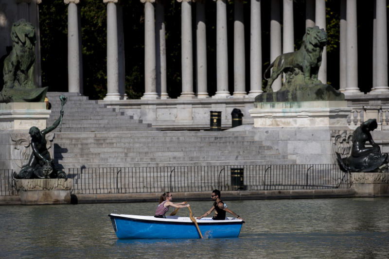 A couple sail a boat during a hot day of summer at the Retiro park in Madrid, Spain, Wednesday, July 29, 2020. The first heat wave of the summer, which will arrive this Thursday and will last at least until next Saturday will leave temperatures over 34 Celsius (104 Fahrenheit). (AP Photo/Manu Fernandez)