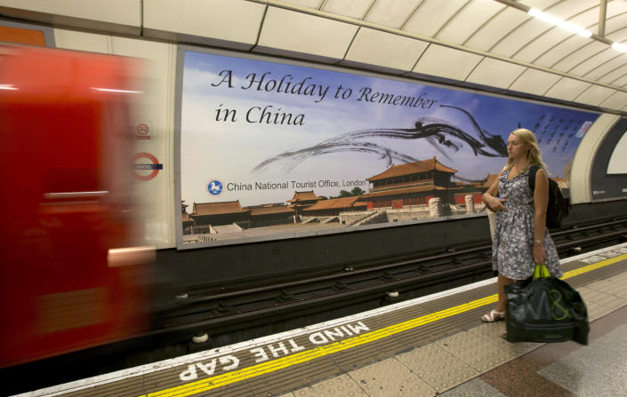 "In this photo taken on Thursday, Aug. 30, 2013, a commuter waits for an incoming tube train while standing in front of a poster for the China National Tourist Office that's part of its ""Beautiful China"" campaign on display at the Angel tube station in Islington, London. China's new tourism slogan ""Beautiful China"" has been criticized by industry experts who say it illustrates a marketing problem that has led to a weakness in growth in foreign visitors over the past few years. (AP Photo/Alastair Grant)"