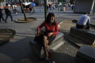 Sex worker Laura, 62, waits for clients outside the Revolution subway station, in Mexico City, Saturday, March 13, 2021. In addition to increased competition and fewer clients, sex workers in the area have to contend with many clients who only want to pay with crack cocaine, or who insist the women smoke with them, leaving recovering drug users like Laura in the difficult position of having to turn down work in order to protect her year of sobriety. (AP Photo/Rebecca Blackwell)