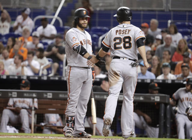 San Francisco Giants' Brandon Crawford, left, greets Buster Posey (28) after Posey scored on a balk by Miami Marlins starting pitcher Wei-Yin Chen during the fifth inning of a baseball game, Monday, June 11, 2018, in Miami. (AP Photo/Lynne Sladky)