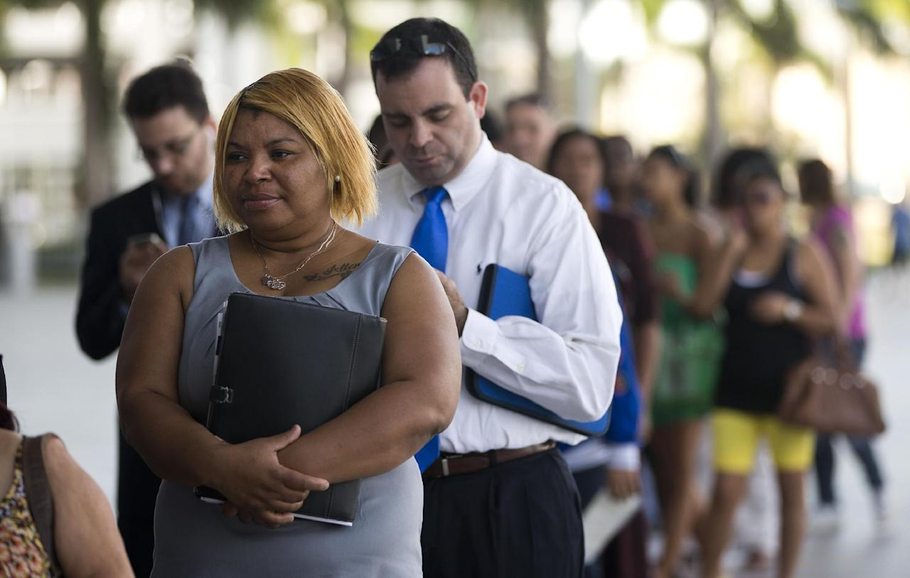 In this Jan. 15, 2013, photo, Racheel Weston, stood in line with a few hundred other job seekers, during the job fair that the Miami Marlins hosted at Marlins Park in Miami. The number of Americans seeking unemployment benefits fell last week to the lowest level in five years, a positive sign that layoffs have fallen and hiring may pick up. (AP Photo/J Pat Carter)