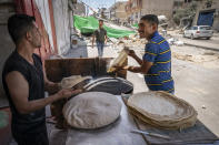 Bakery workers smile as they produce flatbreads at roadside near the debris pile of a building destroyed by an airstrike prior to a cease-fire reached after an 11-day war between Gaza's Hamas rulers and Israel, in Gaza City, Saturday, May 22, 2021. (AP Photo/John Minchillo)