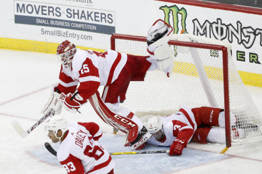 Detroit Red Wings goaltender Jonathan Bernier (45) leaps to avoid Red Wings defenseman Alex Biega (3) who slides into the net during the third period of an NHL hockey game against the New Jersey Devils, Thursday, Feb. 13, 2020, in Newark, N.J. Red Wings defenseman Trevor Daley (83) skates away. (AP Photo/Kathy Willens)