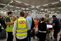 Passengers talk to British government officials at Thomas Cook check-in points at Mallorca Airport after the world's oldest travel firm collapsed, in Palma de Mallorca