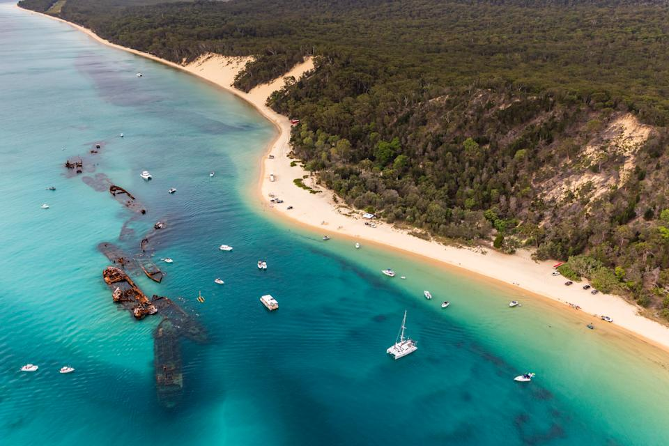 A bird's eye view of Cape Moreton from a helicopter with no doors looking onto beach and white sand formations