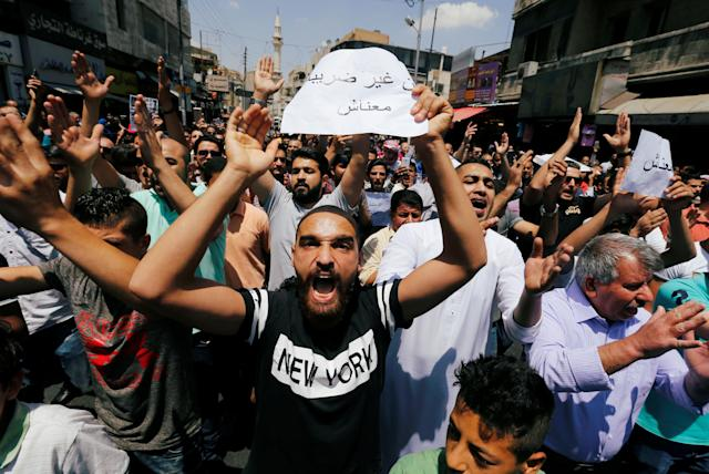 "<p>Protesters chant slogans during a protest against the new income tax law and high fuel prices, in Amman, Jordan June 1, 2018. The banner reads in Arabic ""we do not have money"". (Photo: Muhammad Hamed/Reuters) </p>"