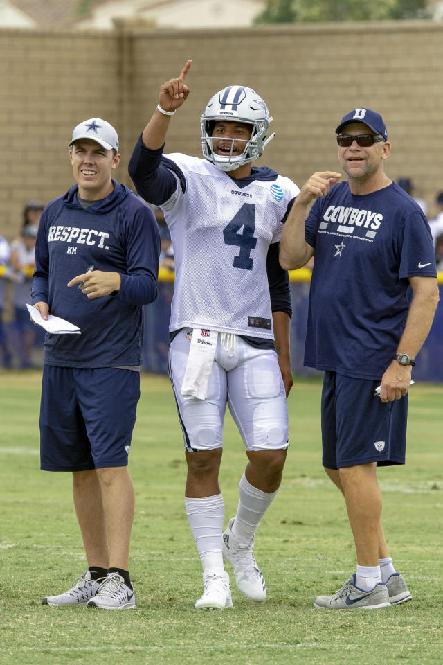 FILE - In this July 28, 2018, file photo, Dallas Cowboys quarterbacks coach Kellen Moore, left, quarterback Dak Prescott (4) and offensive coordinator Scott Linehan, right, talk things over during NFL football training camp in Oxnard, Calif. Nobody close to Moore is surprised he ended up in coaching. Theyve been saying that about him since he was winning high school state championships under his dad, Tom Moore, in Washington. The only surprise is that his younger brother, Fresno State receivers coach Kirby Moore, beat him into coaching by several years. Thats because Kellen Moores NFL career lasted six years despite playing just three regular-season games after going 50-3 as the starter at Boise State. (AP Photo/Gus Ruelas)