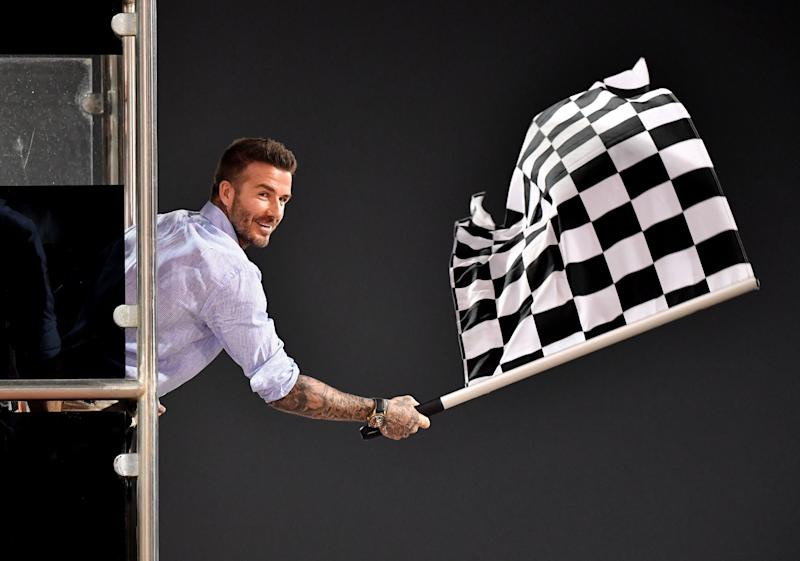 TOPSHOT - Former British football player David Beckham waves the checkered flag as Mercedes' British driver Lewis Hamilton crosses the finish line during the Formula One Bahrain Grand Prix at the Sakhir circuit in the desert south of the Bahraini capital Manama, on March 31, 2019. (Photo by Andrej ISAKOVIC / various sources / AFP) (Photo credit should read ANDREJ ISAKOVIC/AFP/Getty Images)