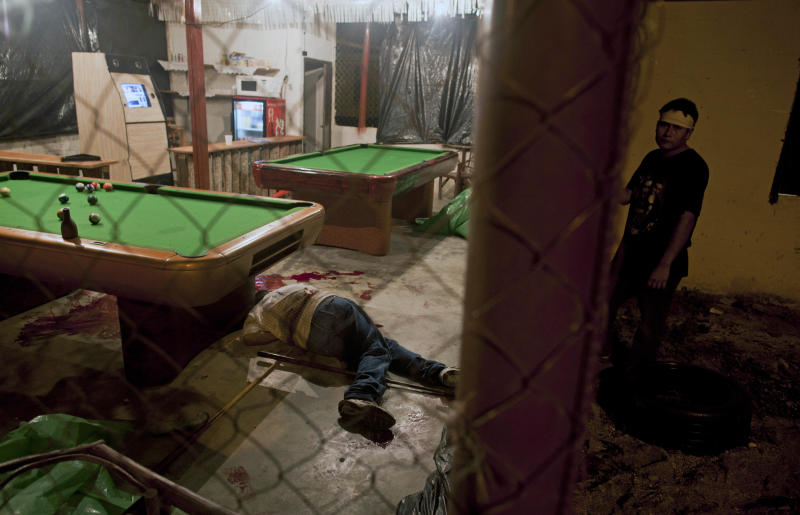 In this March 11, 2012 photo, the body of Wilmer Orbera lies inside a pool hall after an attack by masked assailants in Choloma on the outskirts of San Pedro Sula, Honduras. A wave of violence has made Honduras among the most dangerous places on Earth, with a homicide rate roughly 20 times that of the U.S. rate, according to a 2011 United Nations report. (AP Photo/Esteban Felix)