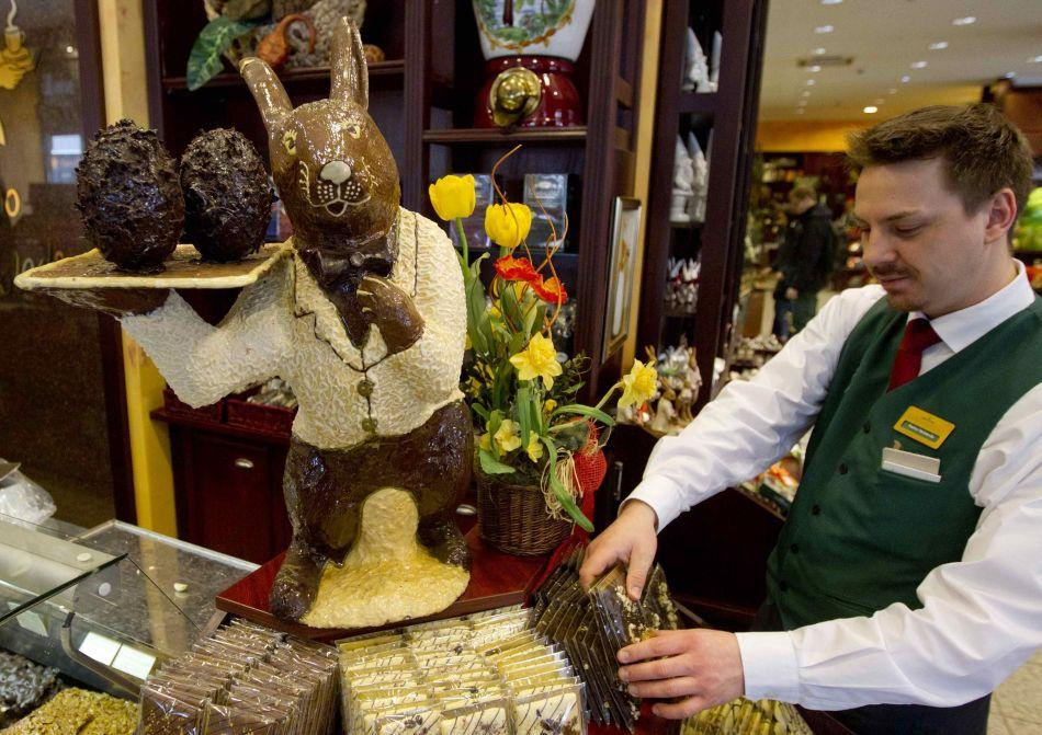 A member of staff arranges chocolate products next to a giant chocolate Easter bunny at the Fassbender and Rausch chocolatier in Berlin