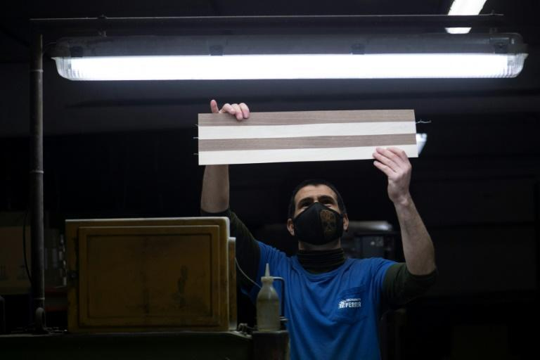 Making chessboards is a slow process -- a worker first selects high-quality wood that is trimmed into long thin sheets of light and dark colours