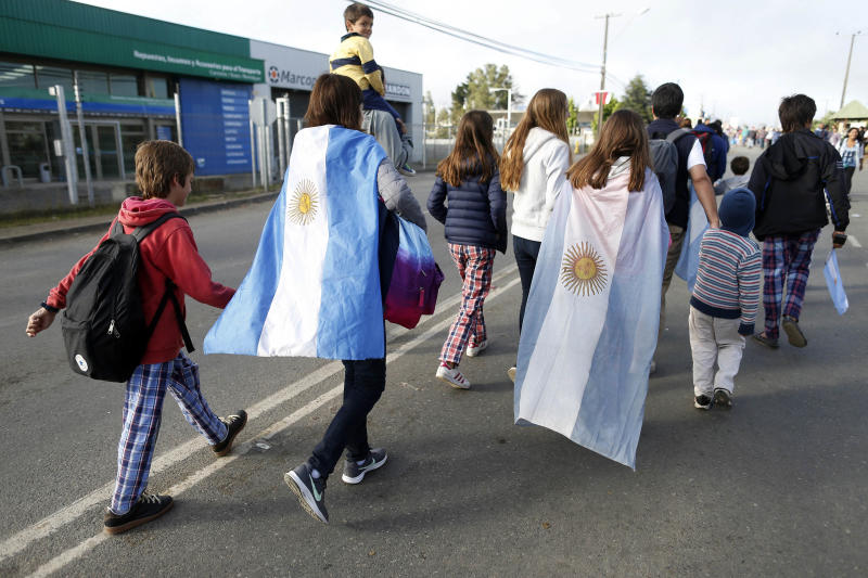 People, some donning Argentina's national flag, walk to the venue at the Maquehue Air Base where Pope Francis will celebrate Mass , in Temuco, Chile, Wednesday, Jan. 17, 2018. Francis heads to the heart of Chile's centuries-old conflict with indigenous peoples to celebrate Mass at the air base which is on contested land that was also used as a detention and torture facility during the country's bloody military dictatorship. (AP Photo/Luis Hidalgo)