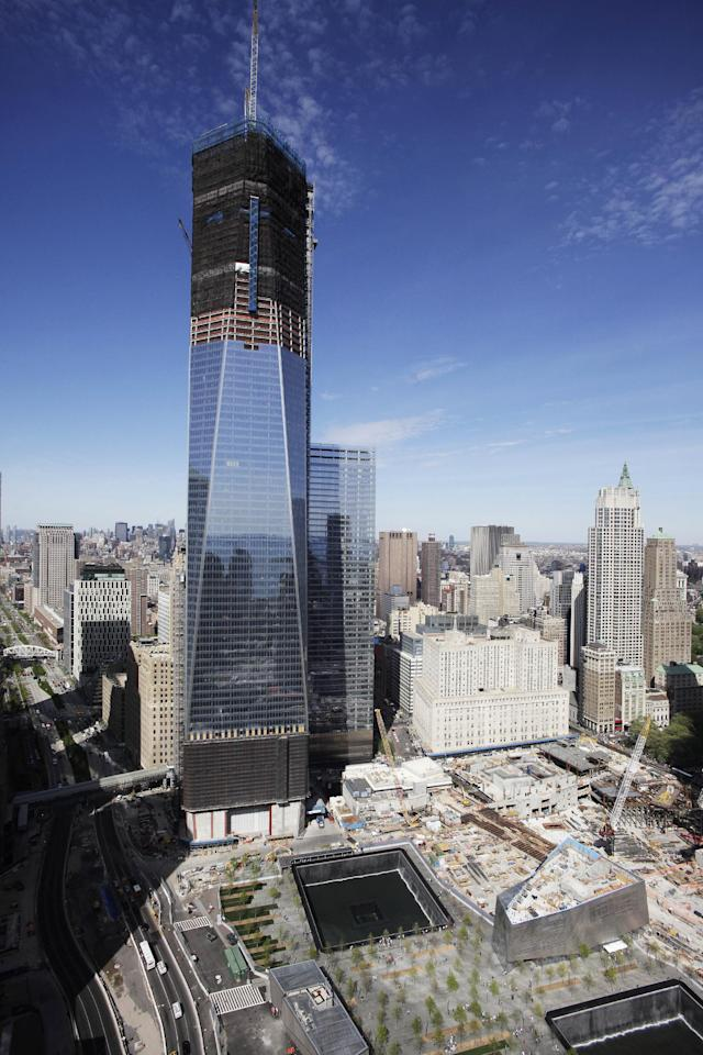 "FILE- In this April 17, 2012, file photo, One World Trade Center, rises above the lower Manhattan skyline and the National September 11 Memorial, lower right, in New York. One World Trade Center, the giant monolith being built to replace the twin towers destroyed in the Sept. 11 attacks, will lay claim to the title of New York City's tallest skyscraper on Monday, April 30, as workers erect steel columns that will make its unfinished skeleton a little over 1,250 feet, just high enough to peak over the observation deck on the Empire State Building. The milestone is a preliminary one. The so-called ""Freedom Tower"" isn't expected to reach its full height for at least another year, at which point it is likely to be declared the tallest building in the U.S. (AP Photo/Mark Lennihan, File)"