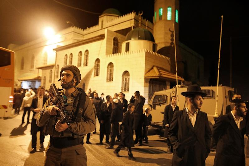 Israeli soldiers stand guard as ultra-Orthodox Jewish men, mostly from the Hasidim Breslov sect, arrive to pray in front of Younis mosque where, according to tradition,  biblical prophets Gad and Nathan are buried in the West Bank village of Halhul