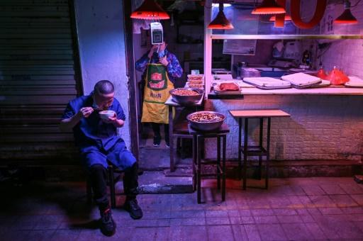 A man eats lunch next to a market stall in Wuhan