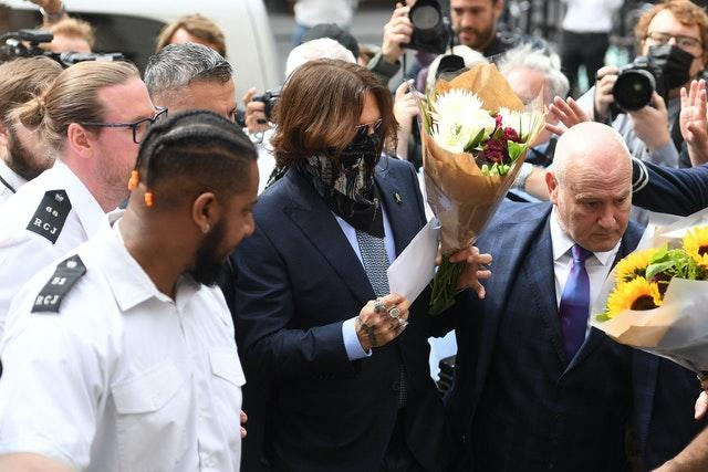 Actor Johnny Depp receives flowers as he arrives at the High Court in London